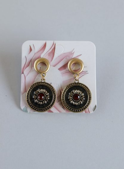 Gold Earrings With Red and Clear Stones Set in a Black Medallion